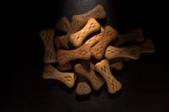 O osso deu forma a cookies ou a deleites do cão, no fundo de madeira escuro fotografia de stock