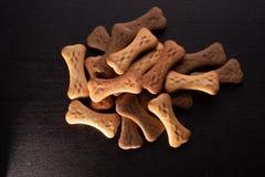 O osso deu forma a cookies ou a deleites do cão, no fundo de madeira escuro fotos de stock