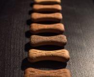 O osso deu forma a cookies ou a deleites do cão, no fundo de madeira escuro imagem de stock royalty free