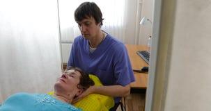 O osteopata faz a massagem do pescoço à mulher idosa vídeos de arquivo