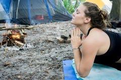O ot do retrato de uma jovem mulher com pose da oração do namaste entrega a ioga do toguether ao acampar na floresta imagens de stock royalty free