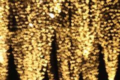 O ouro amarelo coração-deu forma ao branco colorido de suspensão do bokeh da iluminação do fundo do Valentim para o papel de pare foto de stock