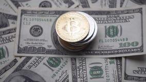 O ouro Bitcoin em uma parte superior do othe inventa o giro em contas de 100 dólares Cryptocurrency virtual mundial do Internet e video estoque