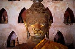 o ouro chapeou estátuas budistas do theravada em um monastério com um pano de seda alaranjado fotos de stock royalty free