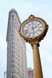 O ouro da construção do ferro de passar roupa e do Fifth Avenue cronometra em New York Foto de Stock Royalty Free