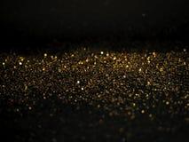 O ouro e a prata brilham com bokeh, fundo preto foto de stock