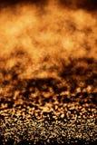 O ouro vislumbra o fundo com luzes douradas e pretas brilhantes spar fotografia de stock royalty free