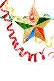 O ouropel comemorativo Multi-coloured e o Natal star em um branco Fotografia de Stock Royalty Free
