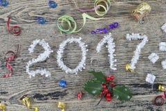 O ouropel do branco do ano 2017 em um fundo de madeira pintado velho com Natal brinca Foto de Stock Royalty Free