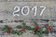 O ouropel do branco do ano 2017 em um fundo de madeira pintado velho com Natal brinca Fotografia de Stock Royalty Free