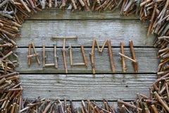 O outono da inscrição com as varas de madeira no fundo de madeira Imagem de Stock Royalty Free