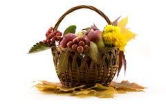 O outono frutifica com folhas amarelas em uma cesta Imagens de Stock Royalty Free