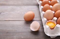 O ovo da galinha quebra-se parcialmente entre outros ovos Ovos da galinha em uns recipientes no fundo de madeira cinzento fotografia de stock royalty free