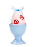 O ovo da páscoa cor-de-rosa está no copo de ovo azul Fotos de Stock Royalty Free