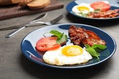 O ovo fritado do estrelado com tomate e bacon serviu imagem de stock royalty free
