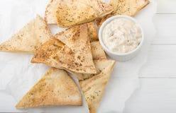O pão árabe caseiro lasca-se no Livro Branco com iogurte Fotos de Stock Royalty Free