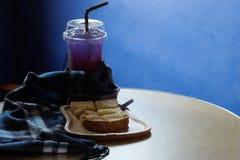 O pão brindado no trey de madeira, a tabela azul, a tabela de madeira e o espaço para escrevem o fraseio imagem de stock