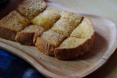 O pão brindado no trey de madeira, a tabela azul, a tabela de madeira e o espaço para escrevem o fraseio foto de stock