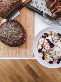O pão caseiro e uma flor endurecem com cobertura branca em uma tabela branca de madeira de cima de Imagens de Stock Royalty Free