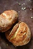 O pão caseiro fresco da farinha inteira do trigo e de centeio com sementes, abóbora e aveia de linho lasca-se em um fundo marrom foto de stock royalty free
