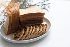 O pão cortado pôs no prato branco, sobre a mesa branca imagem de stock royalty free