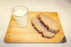 O pão cortou em partes em uma placa de madeira ao lado de um vidro do leite foto de stock royalty free