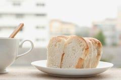 O pão cortou nas fatias em uma placa branca Fotos de Stock Royalty Free