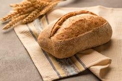 O pão da grão com sementes e a crosta perfumada crocante está em uma toalha fotografia de stock