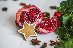 O pão-de-espécie sob a forma das estrelas, romã vermelha do corte, canela, secou limões na tabela branca em um fundo da festão e  Foto de Stock