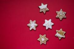 O pão-de-espécie stars com crosta de gelo branca e polvilha no fundo vermelho fotografia de stock royalty free