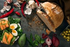 O pão de Sourdough está na tabela Os vegetais são arranjados ao redor Mentira dos ovos e dos salmões nos sanduíches imagem de stock