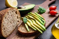 O pão do abacate e de centeio brinda na placa de corte imagens de stock