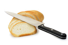 O pão do corte com uma faca Imagem de Stock Royalty Free