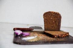 O pão e as cebolas em uma placa de corte isolaram o sal Fotografia de Stock Royalty Free