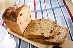 O pão integral inteiro deslizou na placa de madeira na tabela com toalha de mesa Fotos de Stock