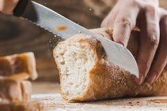 O pão inteiro da grão pôs sobre a placa de madeira da cozinha com um cozinheiro chefe que guarda a faca do ouro para o corte imagem de stock
