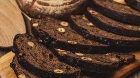 O pão inteiro do multigrain da grão, inteiro e cortado, contém as sementes isoladas no preto video estoque