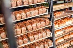 O pão recentemente cozido empilhado e apronta-se empacotando na fábrica Foto de Stock