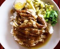 O pé cozido da carne de porco no arroz com pratos laterais é ovo cozido, conservado imagens de stock royalty free