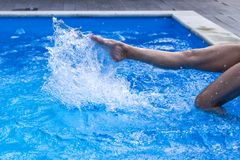 O pé das jovens mulheres na piscina da água, espirra dos pés fêmeas fotografia de stock royalty free