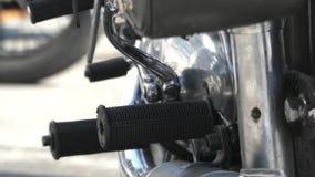 O pé de um homem que tenta ligar uma motocicleta preta video estoque
