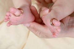 O pé do bebê no ` s da mãe entrega com cuidado com anéis nos dedos do pé imagens de stock royalty free