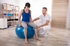O pé ferido de Examining Smiling Woman masculino do fisioterapeuta fotos de stock
