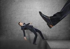 O pé gigante na sapata preta que retrocede homens de negócios pequenos fora da borda, e do ele está caindo para baixo Foto de Stock Royalty Free
