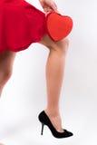 O pé, o vestido vermelho e o coração de uma jovem mulher Foto de Stock Royalty Free
