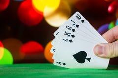 O pôquer do resplendor real carda a combinação no jogo de cartas borrado da fortuna da sorte do casino do fundo Fotos de Stock