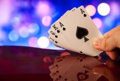 O pôquer do resplendor real carda a combinação na sorte borrada da fortuna do jogo do casino do fundo fotografia de stock