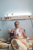 Paciente que senta-se em uma cama imagens de stock royalty free