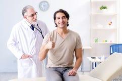 O paciente masculino novo que visita o doutor idoso fotografia de stock royalty free