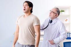 O paciente masculino novo que visita o doutor idoso imagens de stock
